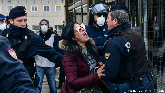 Police hold off an inmate's relative shouting in protest outside the SantAnna prison in Modena, Italy