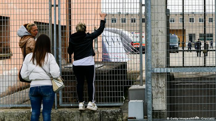 Inmates' relatives stand outside peek into Sant'Anna prison in Modena