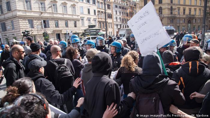 Multidão diante de policiais com capacetes azuis em Roma