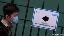 A man wearing a protective face mask walks past an information sign for a Coronavirus 'pod' at a hospital in London, Britain, March 3, 2020. REUTERS/Toby Melville