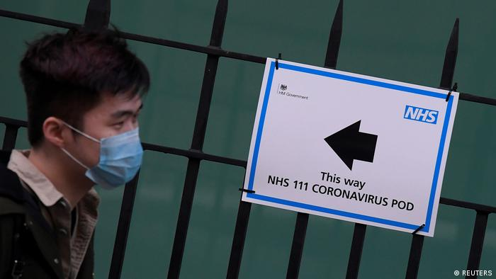 A man wearing a mask walks past an NHS sign for coronavirus testing