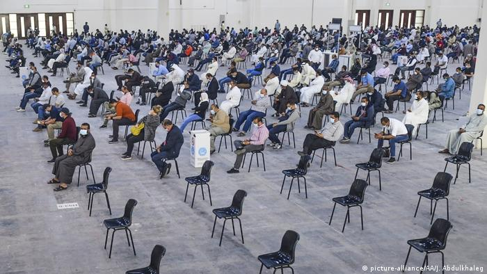 A hall for testing is lined with hundreds of well spaced apart seats. Hundreds in masks sit and wait.