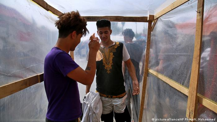 Inside a makeshift wooden frame lined with plastic, a young man sprays down another with a small spray bottle.