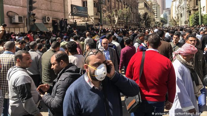 مشهد من القاهرة يوم 8 آذار/ مارس 2020 ويظهر فيه شخص بين الجموع وهو يرتدي كمامة