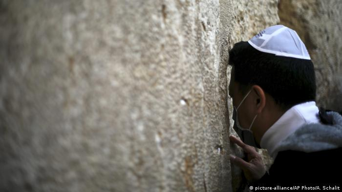 A man wearing a Kippah and medical mask leans in to a crack in a large stone wall