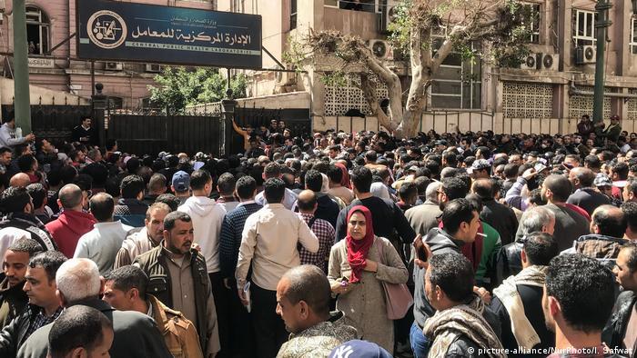 Vor einem großen Steingebäude stehen Hunderte Menschen zusammen, einige tragen Masken