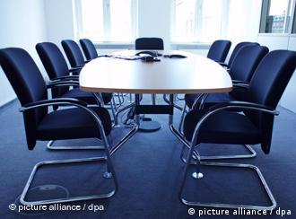 A table surrounded by chairs in a conference room