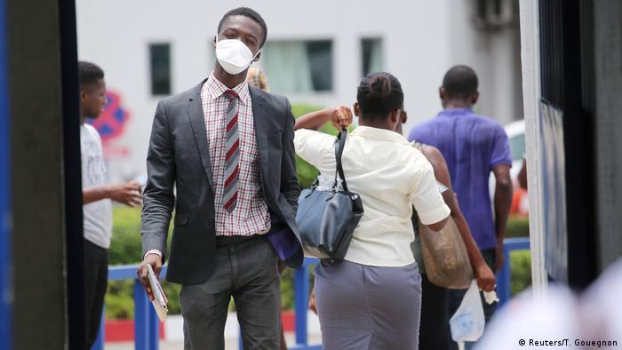 Homem usa máscara em frente a hospital em Abidjan
