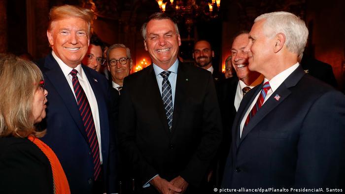 Trump, Bolsonaro and Pence smile at a gathering