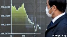 Pedestre olha para uma tela que mostra o movimento do preço das ações da Bolsa de Valores de Tóquio em 12 de março de 2020.