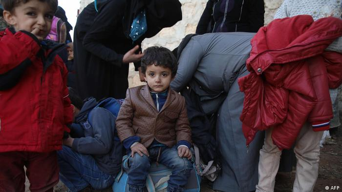 A Syrian child sits on a bad amidst adults
