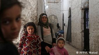 Syrian children smile while standing in a jail that has become a makeshift shelter (AFP/A. Watad)