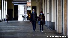 12.3.2020, Turin, Italien, People wearing protective face mask walk in a virtually deserted San Carlo square, on the third day of an unprecedented lockdown across of all Italy imposed to slow the outbreak of coronavirus, in Turin, Italy, March 12, 2020. REUTERS/Massimo Pinca