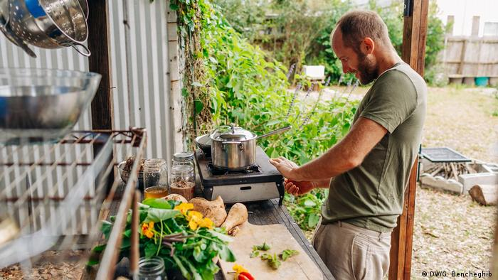 Rob Greenfield cooking on small stove in makeshift kitchen