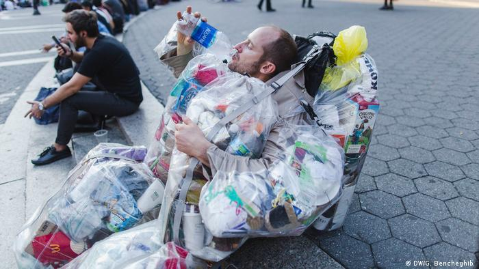 Rob Greenfield drinks out of a plastic bottle while sitting on a curb wearing his trash bags