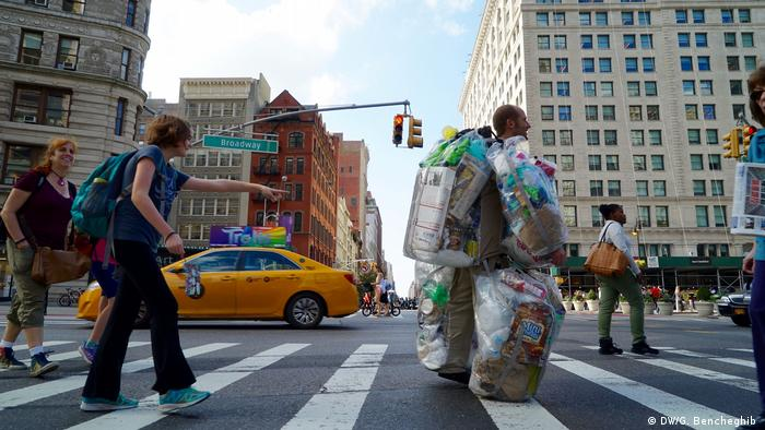 Rob Greenfield crosses a busy New York street wearing trash he produced for a month