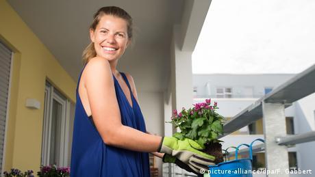 Eine junge Frau bepflanzt ihren Balkon (picture-alliance/dpa/F. Gabbert)