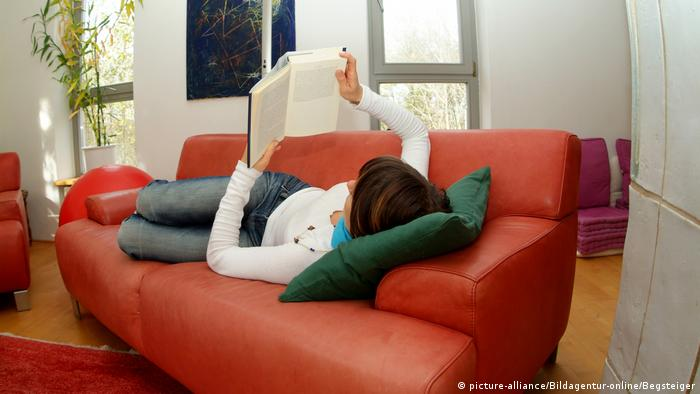 Eine Frau liest auf dem Sofa liegend ein Buch