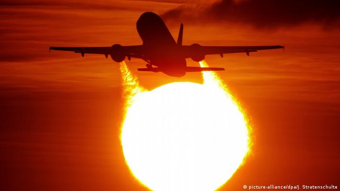 A plane flying through the sky with the sun and a red sky in the background