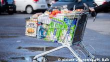 13.03.2020, Bayern, Pullach: Ein Kunde schiebt einen bis zum Rand gefüllten Einkaufswagen über den Parkplatz eines Supermarktes. Foto: Matthias Balk/dpa +++ dpa-Bildfunk +++