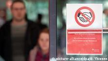 12.03.2020, Nordrhein-Westfalen, Dortmund: «Aus Aktuellem Anlass: Wir schenken Ihnen einen Lächeln, aber verzichten auf den Händedruck» steht auf einer automatischen Glastür der Sparkasse in Dortmund unter einem durchgestrichen Symbol eines Händedrucks. Foto: Bernd Thissen/dpa +++ dpa-Bildfunk +++