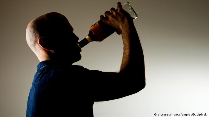 Shadow of a man drinking out of a bottle