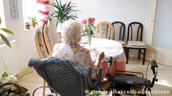 Пожилая женщина сидит за столом в доме престарелых