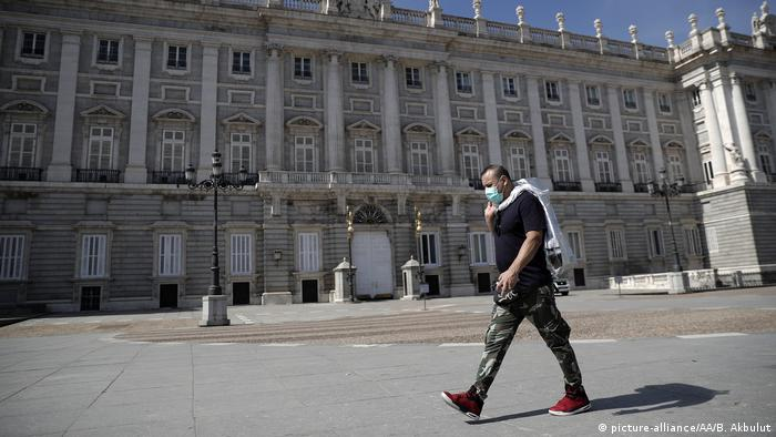 Homem com máscara sanitária caminha diante do Real Palácio de Madri