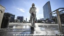 A worker wearing a protective suit disinfects the area in front of the Centrale main railway station, in Milan, Italy, Friday, March 13, 2020. Italians have been experiencing yet further virus-containment restrictions after Premier Giuseppe Conte ordered restaurants, cafes and retail shops closed after imposing a nationwide lockdown on personal movement. For most people, the new coronavirus causes only mild or moderate symptoms. For some it can cause more severe illness. (Claudio Furlan/LaPresse via AP)  