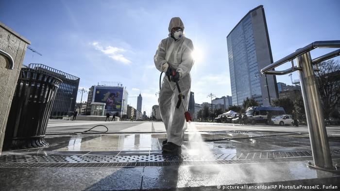 Мужчина в спецодежде дезинфицирует улицу в Милане