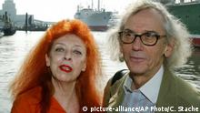 U.S. artists Christo, right, and Jeanne-Claude pose for photographers in front of the ship Cap San Diego during their visit in Hamburg's port on Monday, Aug. 26, 2002. The artists visit the city of Hamburg and will introduce new projects. (AP Photo/Christof Stache) |