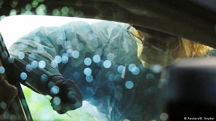 Medical personnel swab a driver's nose at a drive-through coronavirus testing site in Seattle, Washington