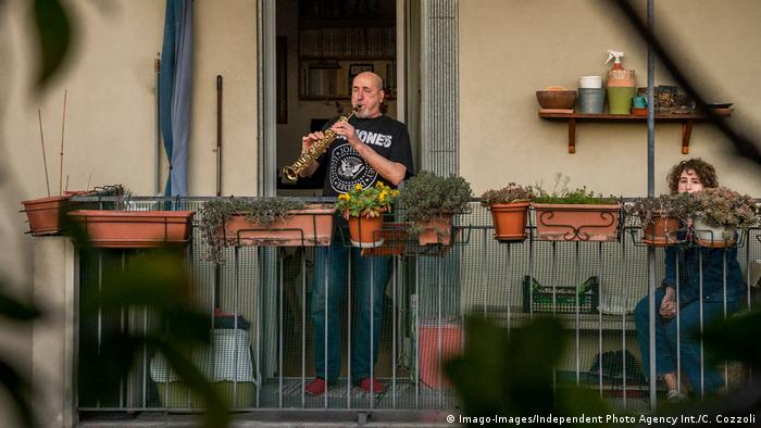 A man plays the clarinet on his balcony in Milan