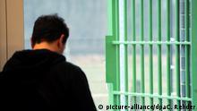 ILLUSTRATION - Ein junger Mann steht an einer Gittertür der Jugendarrestvollzugsanstalt Moltsfelde in Neumünster (Schleswig-Holstein), aufgenommen am 25.02.2013. Foto: Carsten Rehder/dpa | Verwendung weltweit