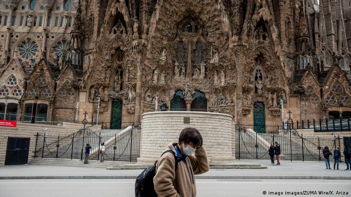 A person wearing a mask walks past the Sagrada Familia on March 14, the first day of a state of emergency in Spain over coronavirus