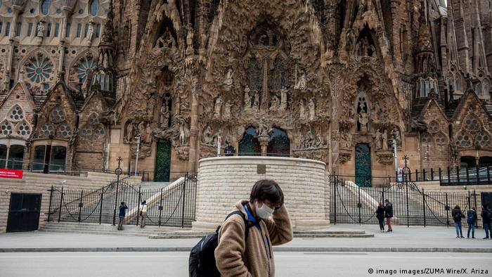 Jovem caminha com máscara em frente à Sagrada Família, em Barcelona