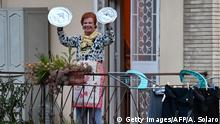 TOPSHOT - A residents uses pot lids to play cymbals as she takes part in a music flash mob called Look out from the window, Rome mine ! (Affacciati alla Finestra, Roma Mia !) aimed at liven up the city's silence during the new coronavirus lockdown, from her balcony in Rome on March 13, 2020. (Photo by Andreas SOLARO / AFP) (Photo by ANDREAS SOLARO/AFP via Getty Images)
