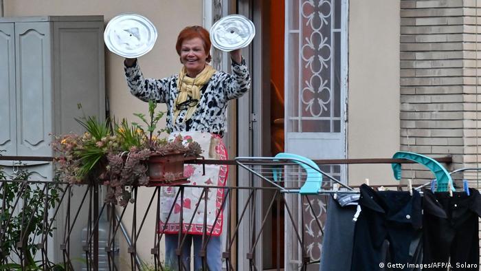 Eine Frau auf einem Balkon hält zwei Topfdeckel in die Höhe