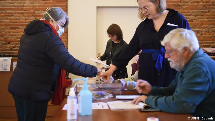 Kommunalwahl in Frankreich in Corona-Zeiten: Hier zeigen Wählerin und Wahlhelfer, wie es - annähernd - richtig gemacht wird (Foto: AFP/E. Cabanis)