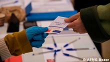An electoral officer wearing plastic gloves holds an electoral card on March 15, 2020, at a polling station in Mulhouse, eastern France, during the first round of mayoral elections in France, as France battling the coronavirus that causes the COVID-19 disease. - Officials have been told to disinfect voting booths and ballot boxes throughout the day, and sinks and hand gels will be made available. People will be urged to get in and out quickly to avoid lines, and floor markings will be laid out to ensure they stay one metre (3.3 feet) from one another. Authorities have already eased proxy voting rules for people at risk or infected with coronavirus and ordered to confine themselves to their homes, as well as for people in retirement homes. People can also come with their own pens for marking ballots. (Photo by SEBASTIEN BOZON / AFP)