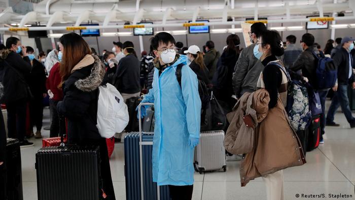 Passageiros com máscaras aguardam embarque em Nova York