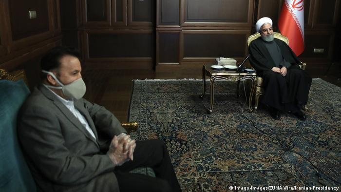 President Rouhani sits in a chair while a minister wears a mask (Imago-Images/ZUMA Wire/Iranian Presidency)