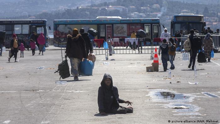 Asylum seekers wait before Greek Navy's transportation ship named Rhodes
