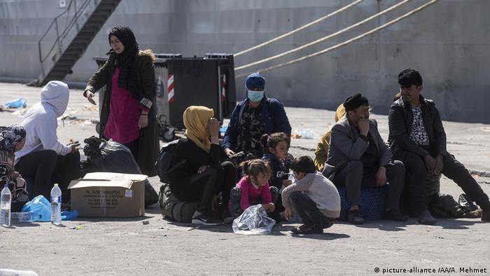 Asylum seekers wait before Greek Navy's transportation ship named Rhodes depart with 450 asylum seekers