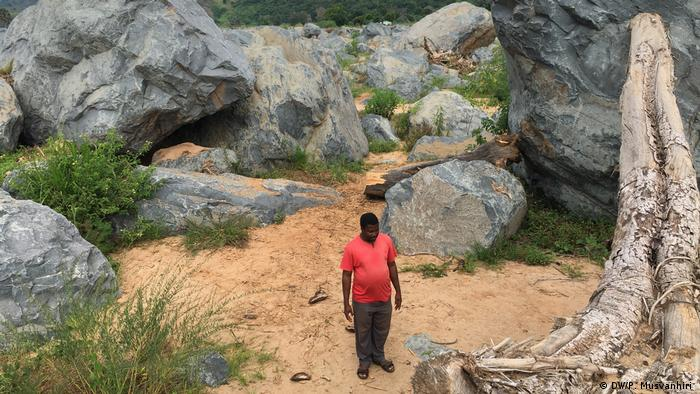 Peter Mutisi stands next to rocks at what used to be his home