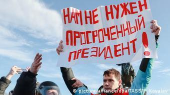 Участник акции протеста держит в руках плакат