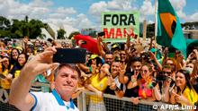 Brazilian President Jair Bolsonaro takes a selfie with supporters in front of the Planalto Palace, after a protest against the National Congress and the Supreme Court, in Brasilia, on March 15, 2020. (Photo by Sergio LIMA / AFP)