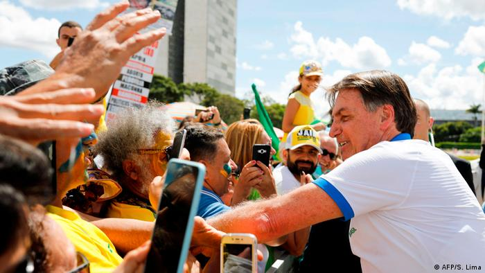 Bolsonaro greets supporters at a rally in Brasilia in mid-March