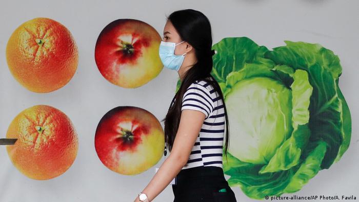 BdTD | Philippinen | Eine Frau mit einer Schutzmaske geht vor einem Einkaufszentrum in Manila (picture-alliance/AP Photo/A. Favila)