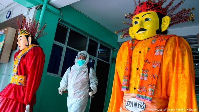 BdTD   Indonesien   Ein Freiwilliger des Indonesischen Roten Kreuzes, der einen Schutzanzug trägt, sprüht Desinfektionsmittel in einer Schule